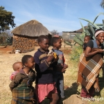 Children stand near their rondevel home and a large aloe plant in Lesotho