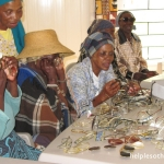 Grandmothers try on glasses bought with sponsor a grandmother program.